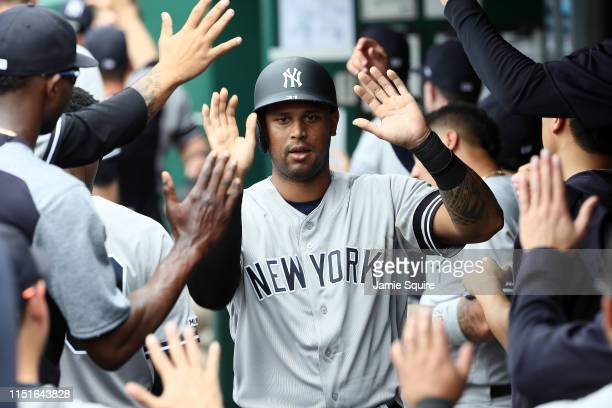 Aaron Hicks of the New York Yankees is congratulated by teammates in the dugout after scoring during the 1st inning of the game against the Kansas...