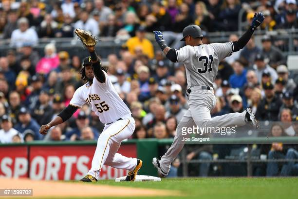 Aaron Hicks of the New York Yankees is out at first base in front of Josh Bell of the Pittsburgh Pirates during the first inning at PNC Park on April...