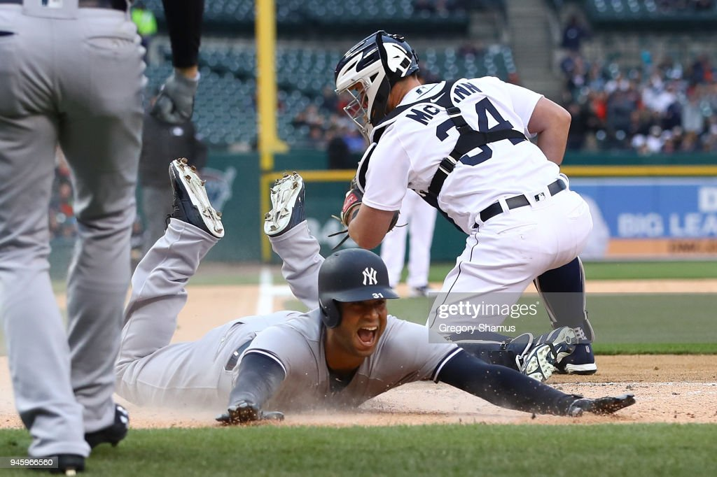 Aaron Hicks #31 of the New York Yankees slides into home plate next to James McCann #34 of the Detroit Tigers for a second inning inside the park home run at Comerica Park on April 13, 2018 in Detroit, Michigan.