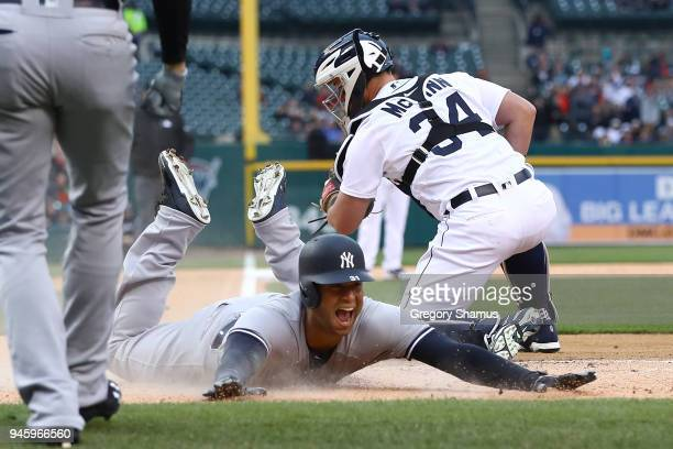 Aaron Hicks of the New York Yankees slides into home plate next to James McCann of the Detroit Tigers for a second inning inside the park home run at...