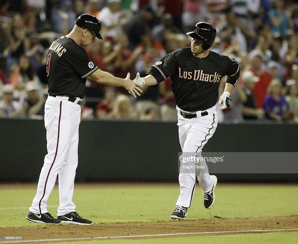 Aaron Hill #2 of the Arizona Diamondbacks is congratulated by third base coach Matt Williams #9 following his solo home run against the Colorado Rockies during the seventh inning of a MLB game at Chase Field on September 14, 2013 in Phoenix, Arizona.
