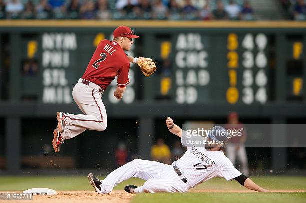 Aaron Hill of the Arizona Diamondbacks leaps on a double play attempt after forcing out the sliding Todd Helton of the Colorado Rockies in the ninth...