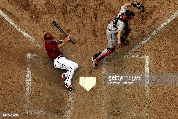 Aaron Hill of the Arizona Diamondbacks safely slides in to score a run past catcher Buster Posey of the San Francisco Giants during the seventh...