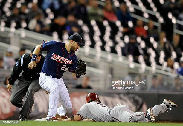 Aaron Hill of the Arizona Diamondbacks steals third base as Trevor Plouffe of the Minnesota Twins fields the late throw during the eighth inning of...