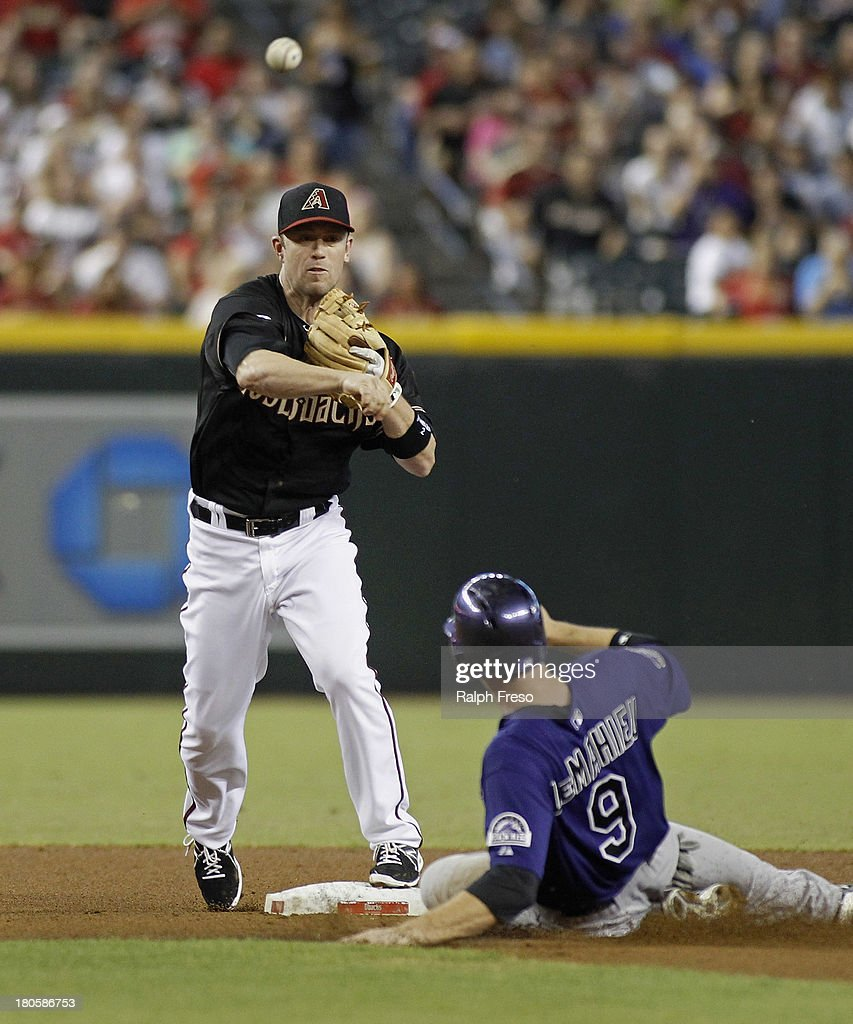 Aaron Hill #2 of the Arizona Diamondbacks throws to first after forcing out D.J. LeMahieu #9 of the Colorado Rockies to complete a double play during the first inning of a MLB game at Chase Field on September 14, 2013 in Phoenix, Arizona.