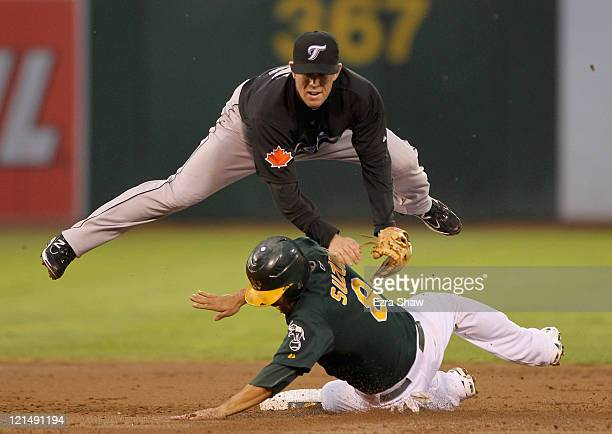 Aaron Hill of the Toronto Blue Jays attempts to turn a double play as Kurt Suzuki of the Oakland Athletics slides in to second base during the second...