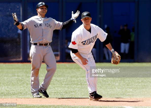 Aaron Hill of the Toronto Blue Jays makes the double play against Nick Swisher of the New York Yankees at the Rogers Centre during a MLB game June 5...