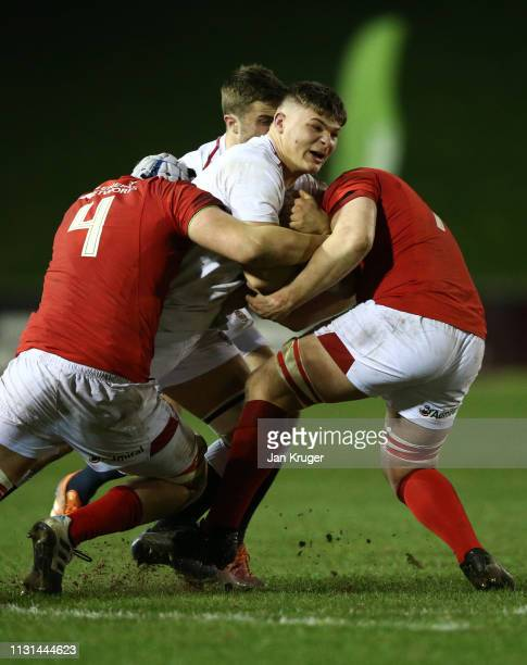 Aaron Hinkley of England is tackled by Ed Scragg and Jac Morgan of Wales during the Under 20 Six Nations Championships match between Wales U20 and...