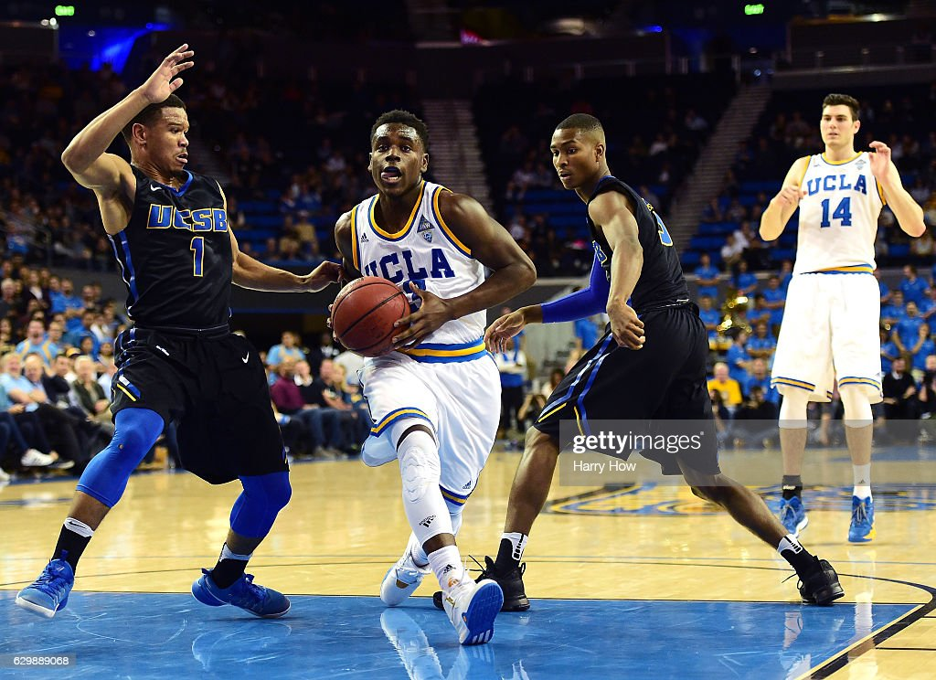 Aaron Holiday #3 of the UCLA Bruins drives between Eric Childress #1 and Clifton Powell #3 of the UC Santa Barbara Gauchos during a 102-62 win over the UC Santa Barbara Gauchos at Pauley Pavilion on December 14, 2016 in Los Angeles, California.