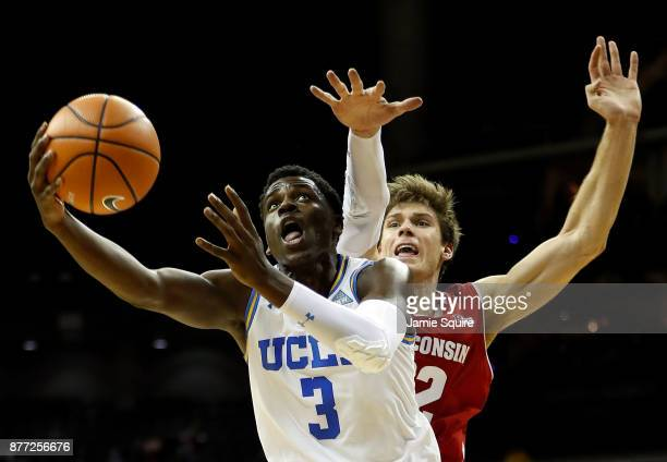 Aaron Holiday of the UCLA Bruins drives toward the basket as Ethan Happ of the Wisconsin Badgers defends during the National Collegiate Basketball...