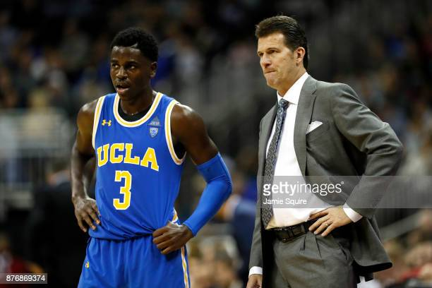 Aaron Holiday of the UCLA Bruins talks with head coach Steve Alford during the National Collegiate Basketball Hall Of Fame Classic game against the...
