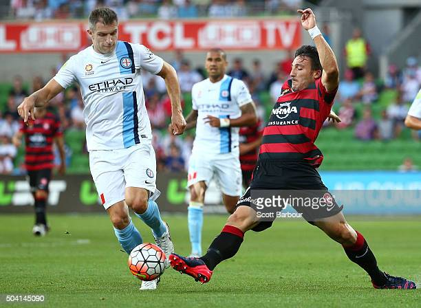 Aaron Hughes of City FC and Federico Piovaccari of the Wanderers compete for the ball during the round 14 ALeague match between Melbourne City FC and...