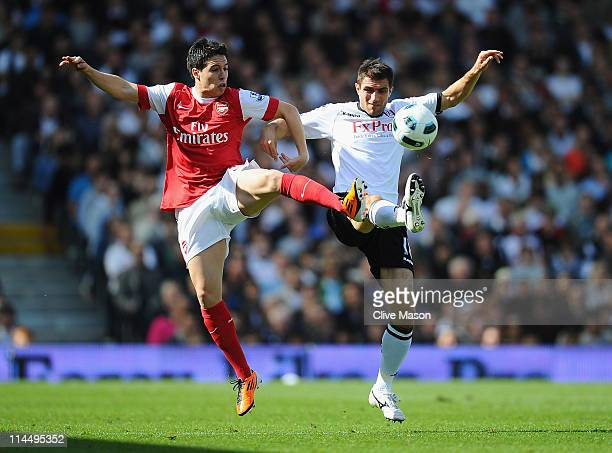 Aaron Hughes of Fulham and Samir Nasri of Arsenal compete for the ball during the Barclays Premier League match between Fulham and Arsenal at Craven...
