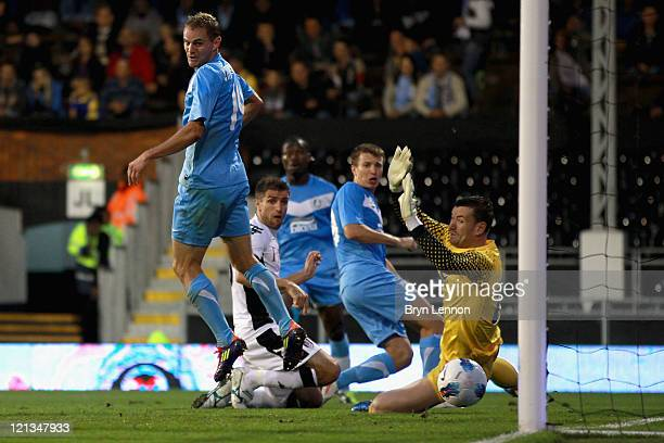 Aaron Hughes of Fulham scores the opening goal past Jan Lastuvka of FC Dnipro during the UEFA Europa League PlayOff round qualifying first leg match...