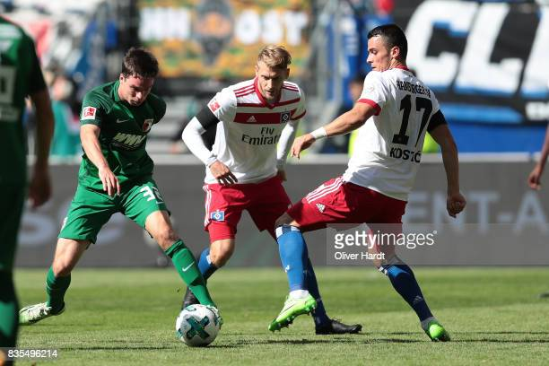 Aaron Hunt and Filip Kostic of Hamburg and Raphael Framberger of Augsburg compete for the ball during the Bundesliga match between Hamburger SV and...