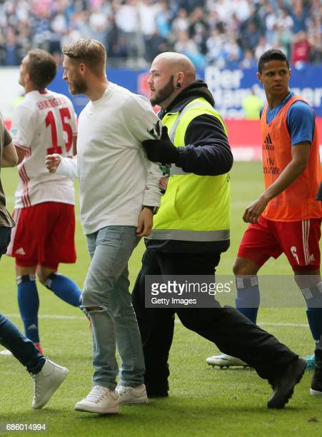 Aaron Hunt is being led away by a security guard after he celebrated their teams second goal during the Bundesliga match between Hamburger SV and VfL...