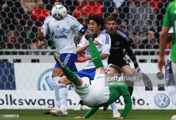 Aaron Hunt of Bremen and Atsuto Uchida of Schalke battle for the ball during the Bundesliga match between SV Werder Bremen and FC Schalke 04 at Weser...