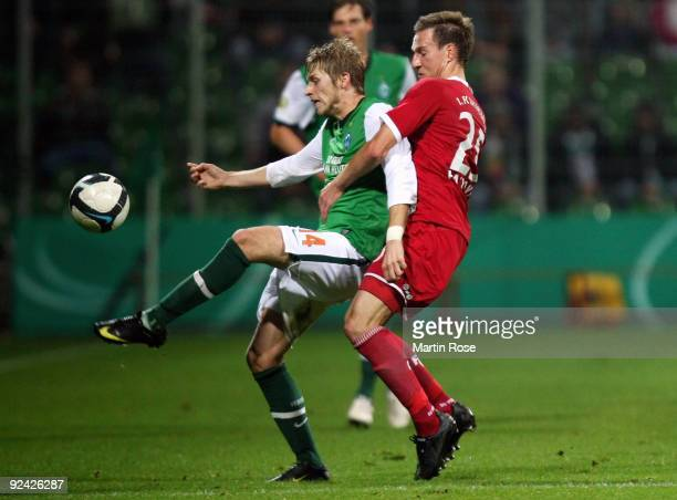Aaron Hunt of Bremen and Daniel Pavlovic of Kaiserslautern battle for the ball during the DFB Cup round of 16 match between between Werder Bremen and...