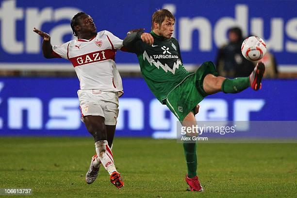Aaron Hunt of Bremen is challenged by Arthur Boka of Stuttgart during the Bundesliga match between VfB Stuttgart and SV Werder Bremen at the...