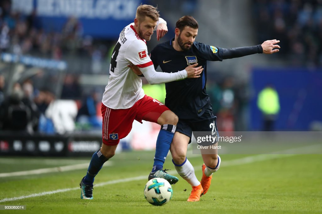Aaron Hunt (L) of Hamburg and Marvin Plattenhardt (R) of Berlin compete for the ball during the Bundesliga match between Hamburger SV and Hertha BSC at Volksparkstadion on March 17, 2018 in Hamburg, Germany.