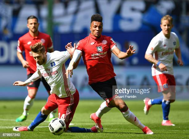 Aaron Hunt of Hamburg is challenged by JeanPhilippe Gbamin of Mainz during the Bundesliga match between Hamburger SV and 1 FSV Mainz 05 at...