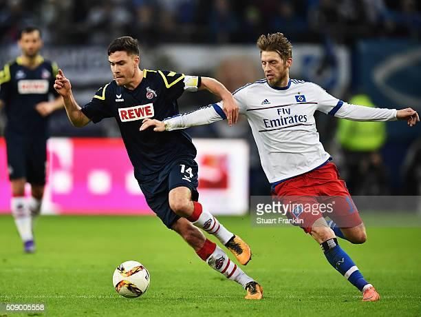 Aaron Hunt of Hamburg is challenged by Jonas Hector of Cologne during the Bundesliga match between Hamburger SV and 1 FC Koeln at Volksparkstadion on...