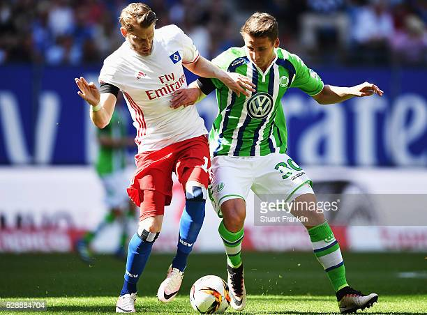 Aaron Hunt of Hamburg is challenged by Paul Seguin of Wolfsburg during the Bundesliga match between Hamburger SV and VfL Wolfsburg at the Volkspark...