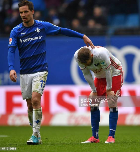 Aaron Hunt of Hamburg is consoled by Sandro Sirigu of Darmstadt during the Bundesliga match between Hamburger SV and SV Darmstadt 98 at...