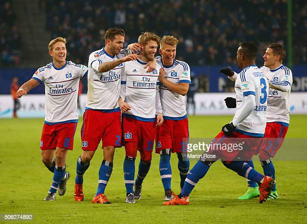 Aaron Hunt of SV Hamburg is congratulated by team mates as his free kick leads to an own goal by Xabi Alonso of Bayern Munich for their equaliser...