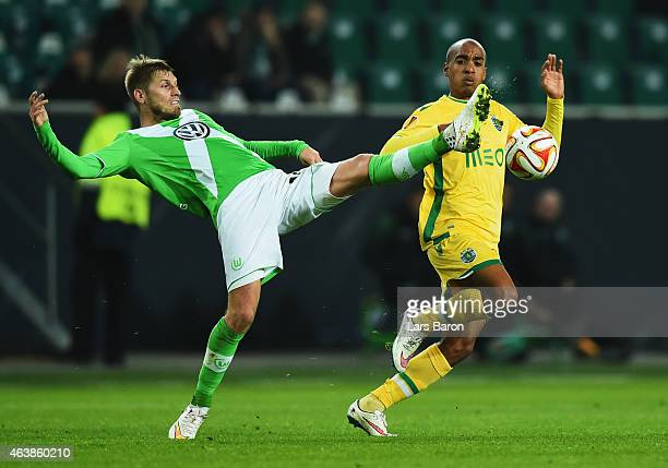 Aaron Hunt of VfL Wolfsburg stretches for the ball ahead of Joao Mario of Sporting Lisbon during the UEFA Europa League Round of 32 first leg match...