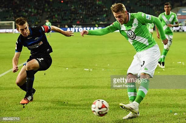 Aaron Hunt of Wolfsburg is challenged by Uwe Huenemeier of Paderborn during the Bundesliga match between VfL Wolfsburg and SC Paderborn 07 at...