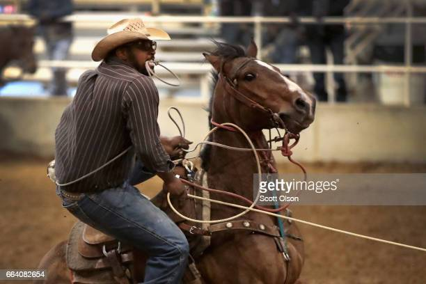 Aaron Johnson competes in the calf roping event at the Bill Pickett Invitational Rodeo on March 31 2017 in Memphis Tennessee The Bill Pickett Rodeo...