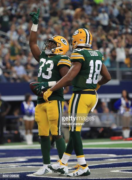 Aaron Jones celebrates a touchdown with Randall Cobb of the Green Bay Packers in the second quarter against the Dallas Cowboys at ATT Stadium on...