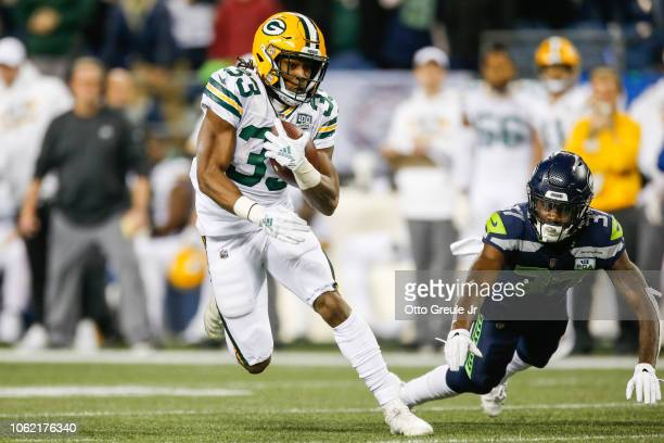 Aaron Jones of the Green Bay Packers avoids a tackle by Tre Flowers of the Seattle Seahawks in the second half at CenturyLink Field on November 15...