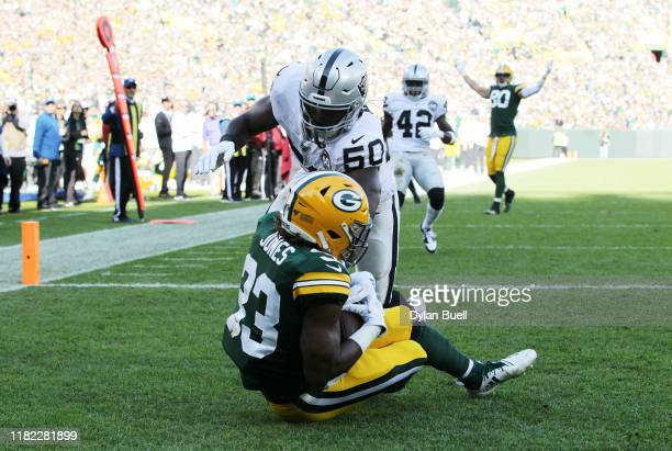 Aaron Jones of the Green Bay Packers catches a touchdown pass against Nicholas Morrow of the Oakland Raiders during the first quarter in the game at...
