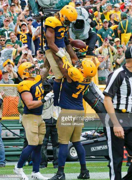 Aaron Jones of the Green Bay Packers celebrates with Elgton Jenkins and Danny Vitale after his touchdown during the third quarter against the Denver...