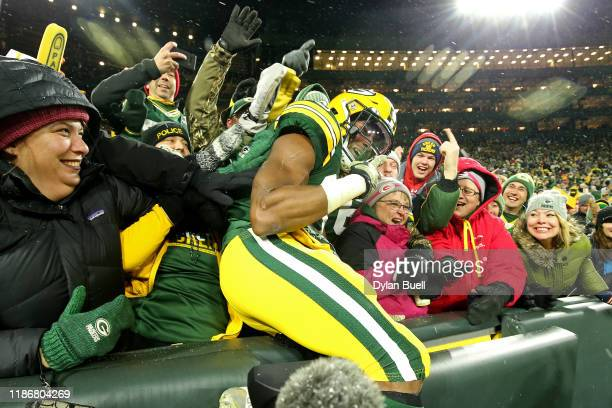 Aaron Jones of the Green Bay Packers celebrates with fans after scoring a 13 yard touchdown against the Carolina Panthers during the third quarter in...