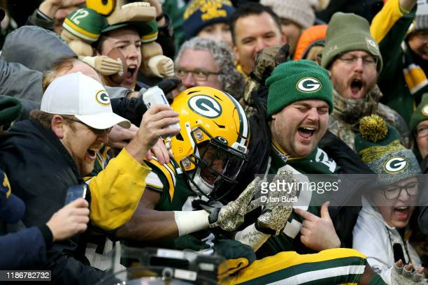 Aaron Jones of the Green Bay Packers celebrates with fans after scoring a 5 yard touchdown against the Carolina Panthers during the first quarter in...