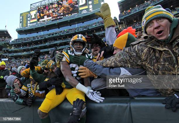 Aaron Jones of the Green Bay Packers celebrates with fans after scoring a touchdown during the second half of a game against the Atlanta Falcons at...