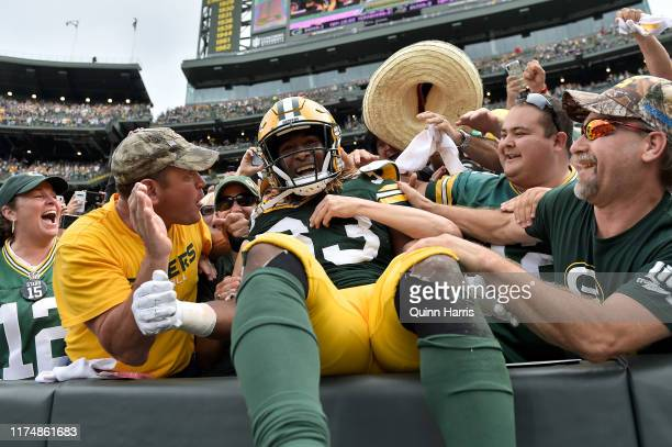 Aaron Jones of the Green Bay Packers celebrates with fans after scoring a touchdown in the second quarter against the Minnesota Vikings at Lambeau...