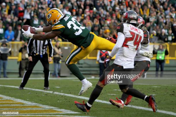 Aaron Jones of the Green Bay Packers dives into the end zone to score a touchdown to beat the Tampa Bay Buccaneers 2620 in overtime at Lambeau Field...