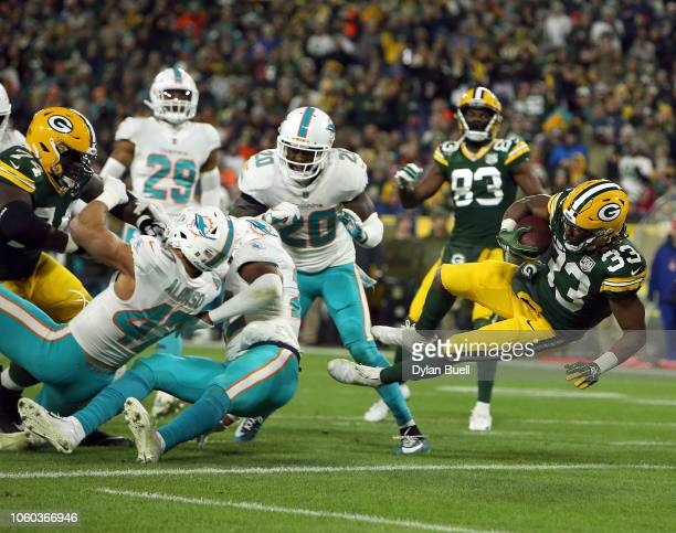 Aaron Jones of the Green Bay Packers dives into the endzone to score a touchdown during the second half of a game against the Miami Dolphins at...