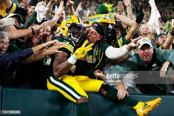 Aaron Jones of the Green Bay Packers does the Lambeau Leap to celebrate his third touchdown of the night against the Detroit Lions during the second...