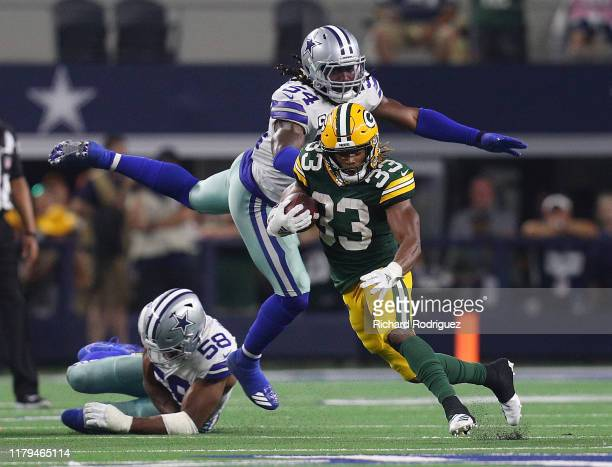 Aaron Jones of the Green Bay Packers evades Jaylon Smith and Robert Quinn of the Dallas Cowboys in the fourth quarter at ATT Stadium on October 06...