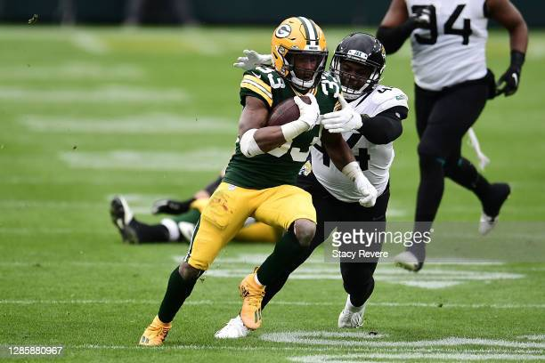 Aaron Jones of the Green Bay Packers is brought down by Myles Jack of the Jacksonville Jaguars during a game at Lambeau Field on November 15, 2020 in...