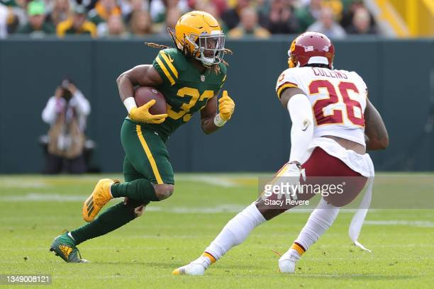 Aaron Jones of the Green Bay Packers is pursued by Landon Collins of the Washington Football Team during a game at Lambeau Field on October 24, 2021...
