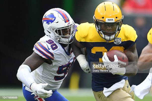 Aaron Jones of the Green Bay Packers is pursued by Shaq Lawson of the Buffalo Bills during a game at Lambeau Field on September 30 2018 in Green Bay...
