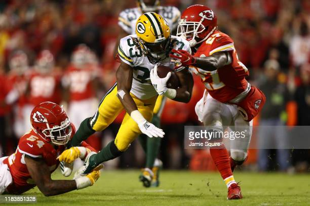 Aaron Jones of the Green Bay Packers is tackled by Damien Wilson and Rashad Fenton of the Kansas City Chiefs during their NFL game at Arrowhead...
