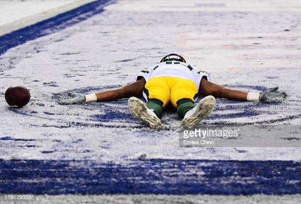Aaron Jones of the Green Bay Packers makes a snow angel in the second half of their game against the New York Giants at MetLife Stadium on December...