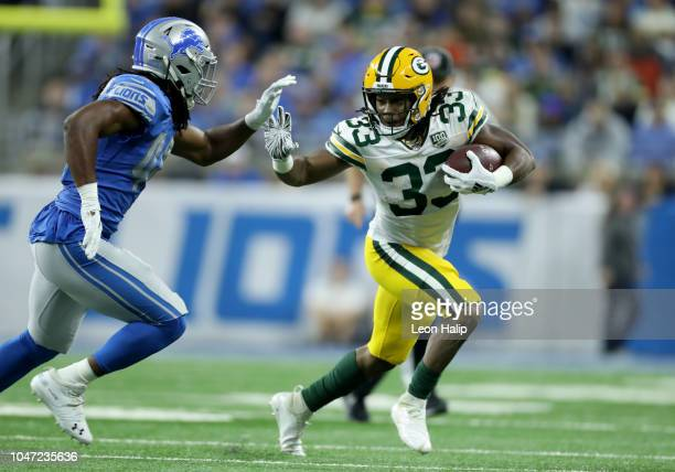 Aaron Jones of the Green Bay Packers runs against Jalen ReevesMaybin of the Detroit Lions during the second half at Ford Field on October 7 2018 in...